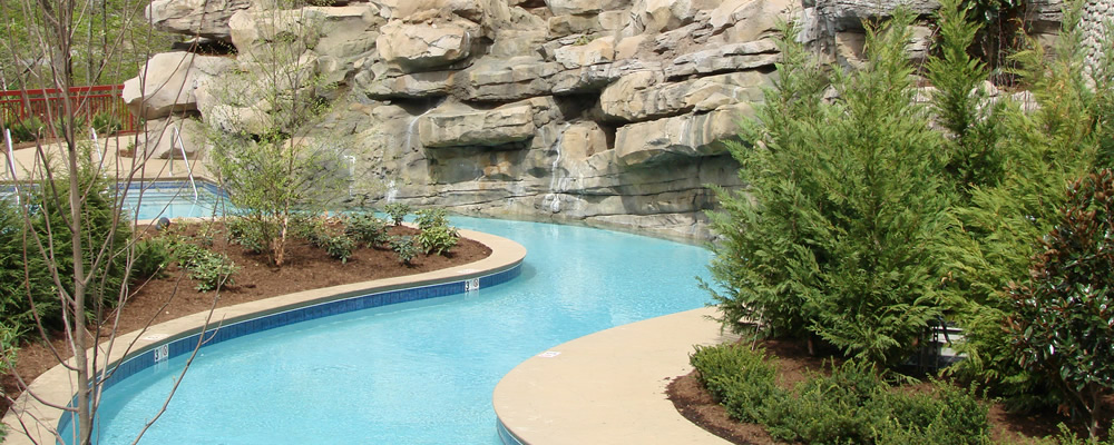 Backyard Lazy River with landscaping and rock wall